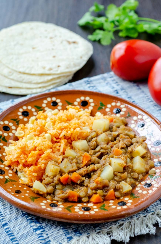 vegan picadillo and mexican rice in a clay plate on top of a striped blue placemat with tortillas and tomates in the background