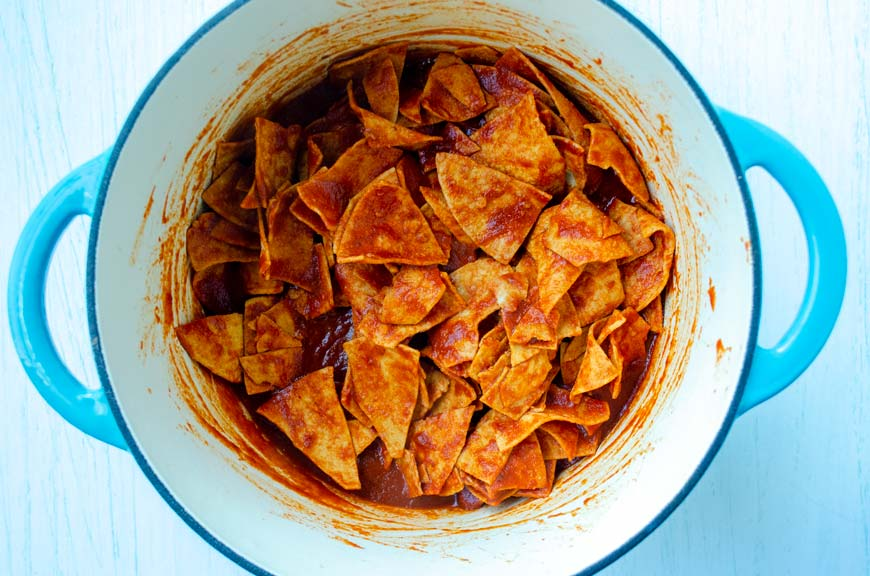 tortilla chips coated in guajilllo chile sauce in a turquoise pot