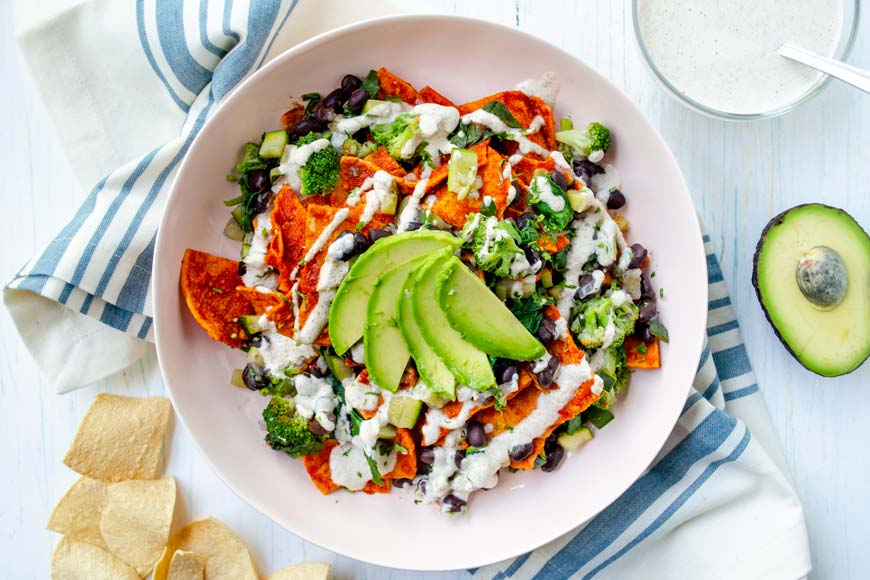 vegan chilaquiles in a pink bowl over a white towel with blue stripes with avocado fan on top