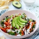 vertical photo of vegan chilaquiles in a pink bowl drizzled with almond crema on a blue and white towel
