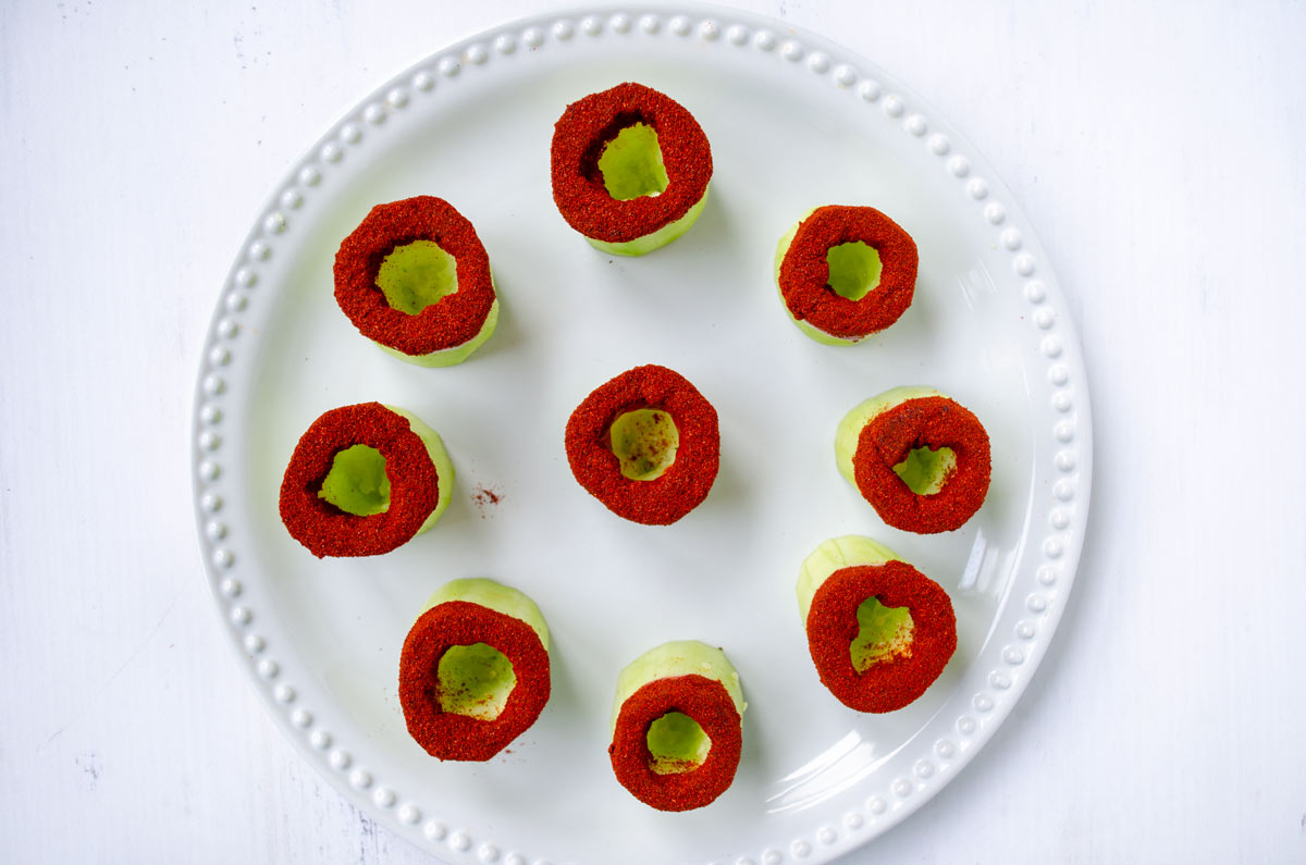 cucumber cups with chile rim on a white plate with dotted rim