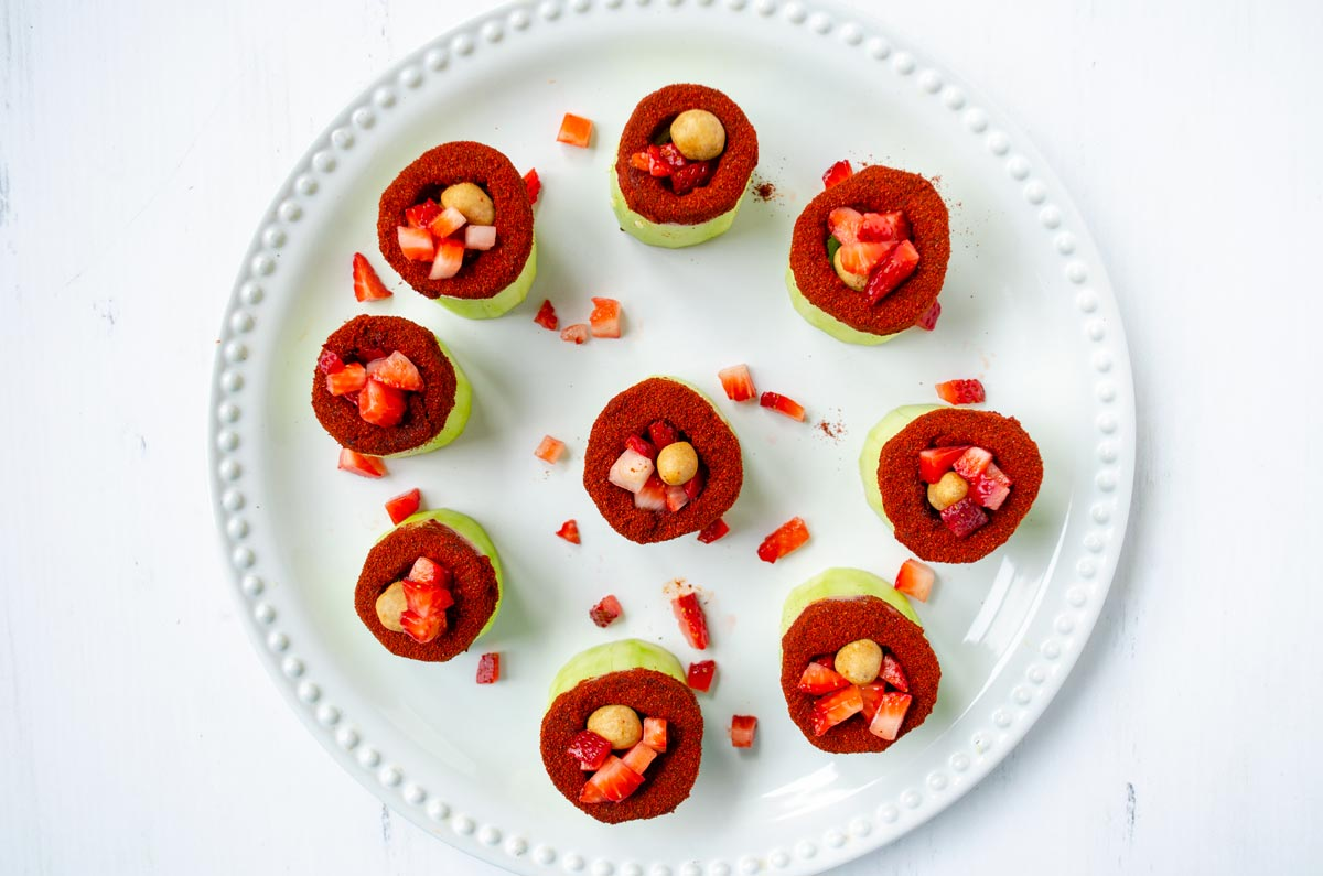 chile covered cucumber cups filled with peanuts and strawberries