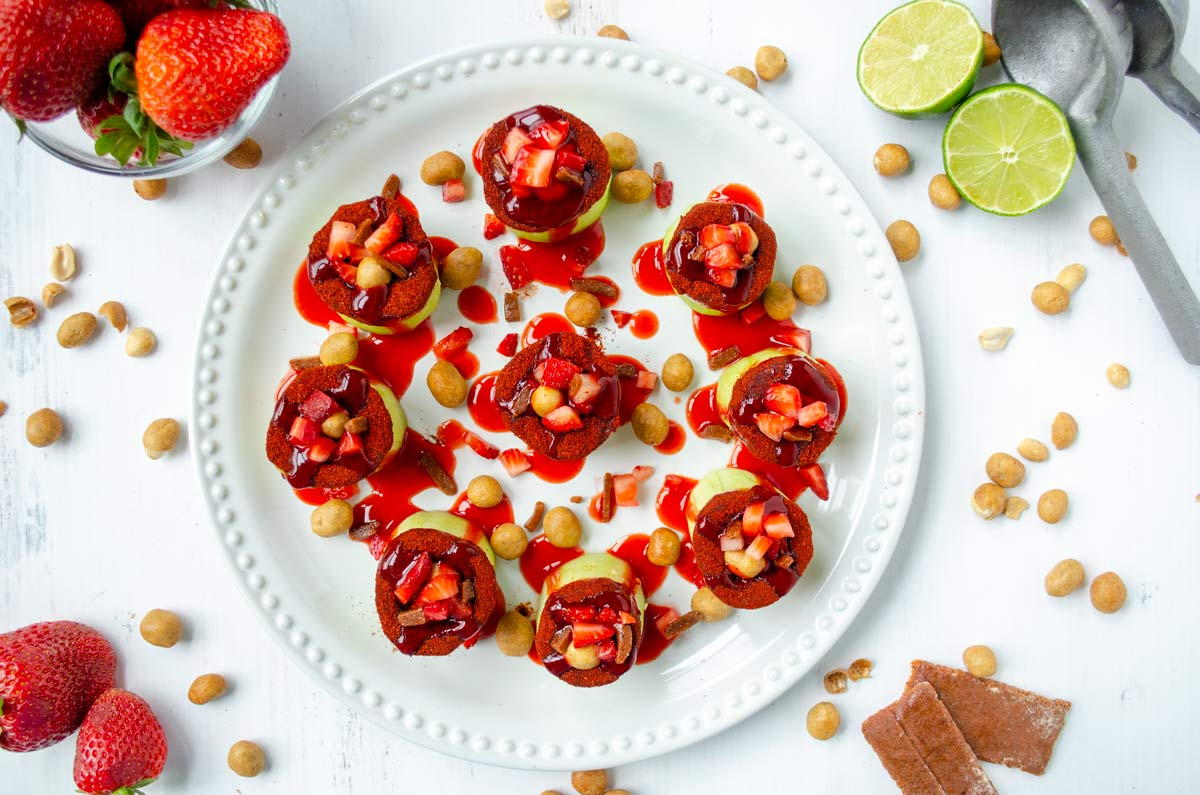 pepinos locos on a white plate with chamoy poured over them surrounded by strawberries and limes