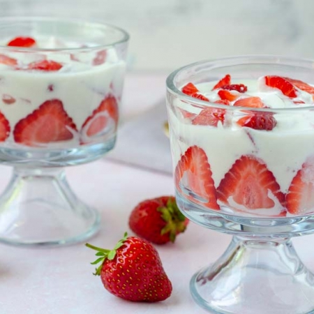 two glass cups filled with fresas con crema on a pink background surrounded by strawberries