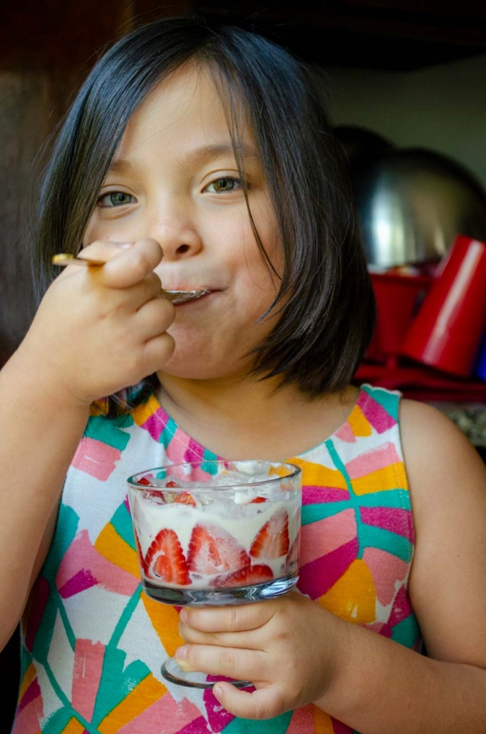 a lovely little girl in a multi-colored dress eating fresas con crema