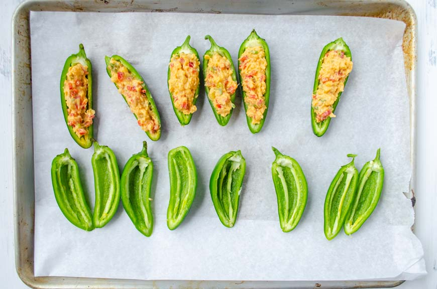 jalapenos cut in half on a sheet tray filled with chickpea mix