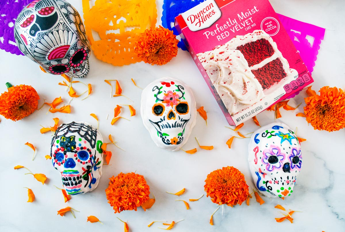 sugar skull cakes on marble background with flowers