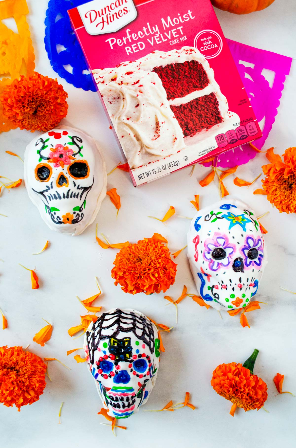 3 cake skulls on a marble background with flowers