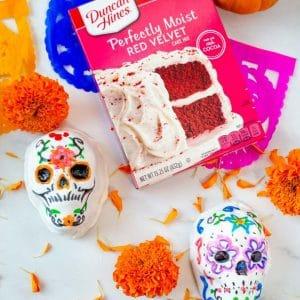 two mini cake sugar skulls decorated for dia de muertos