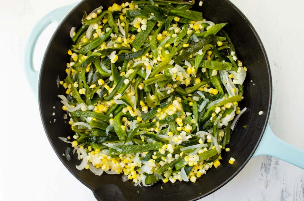 poblano, corn, and onion cooking in cast iron pan