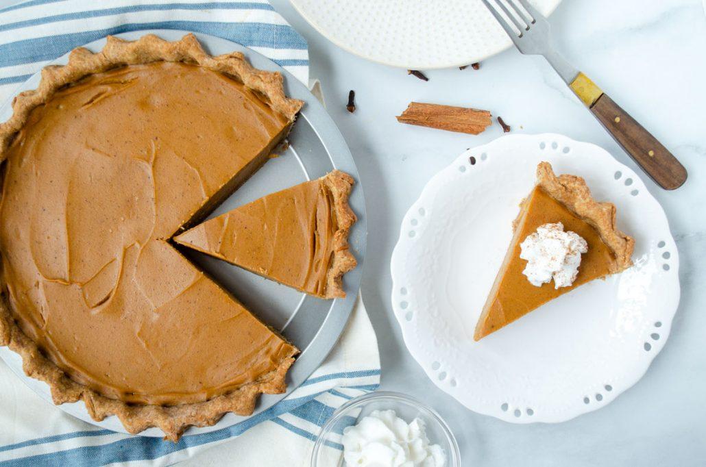 one slice of sweet potato pie beside whole pie