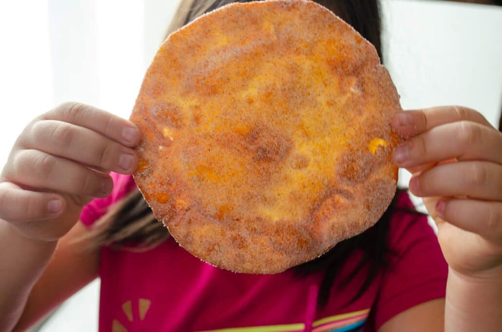 girl holding a buñuelo as big as her face