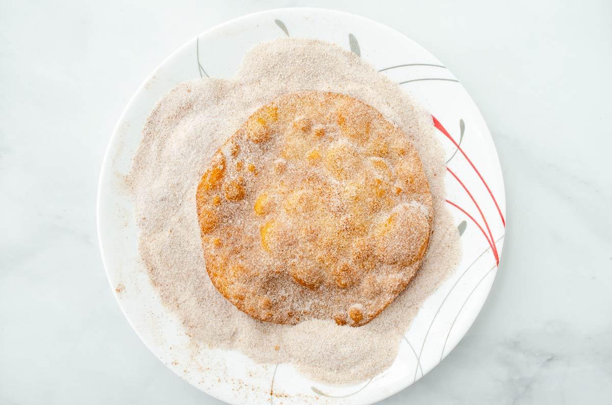 fried buñuelo dipped in cinnamon sugar