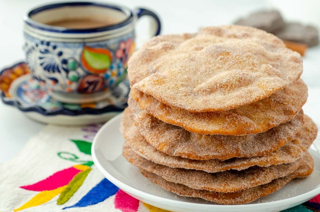 a stack of Mexican buñuelos on a white plate talavera cup in background
