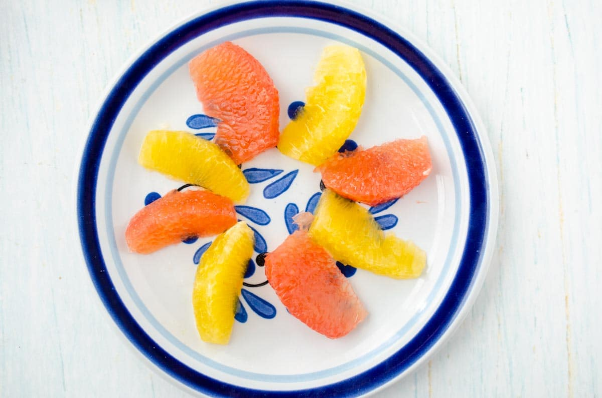 a blue plate with orange and grapefruit segments