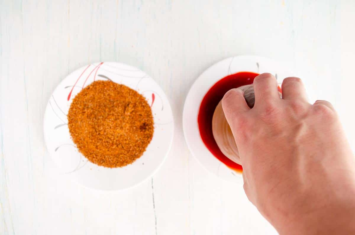 dipping a cantarito in chamoy beside a plate of chile powder