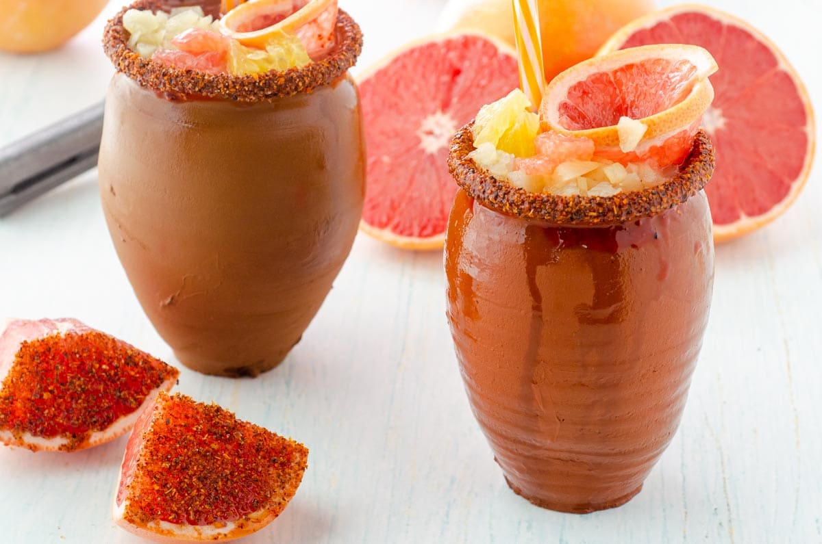 cantarito loco clay cup filled with fruity drink, grapefruit garnish