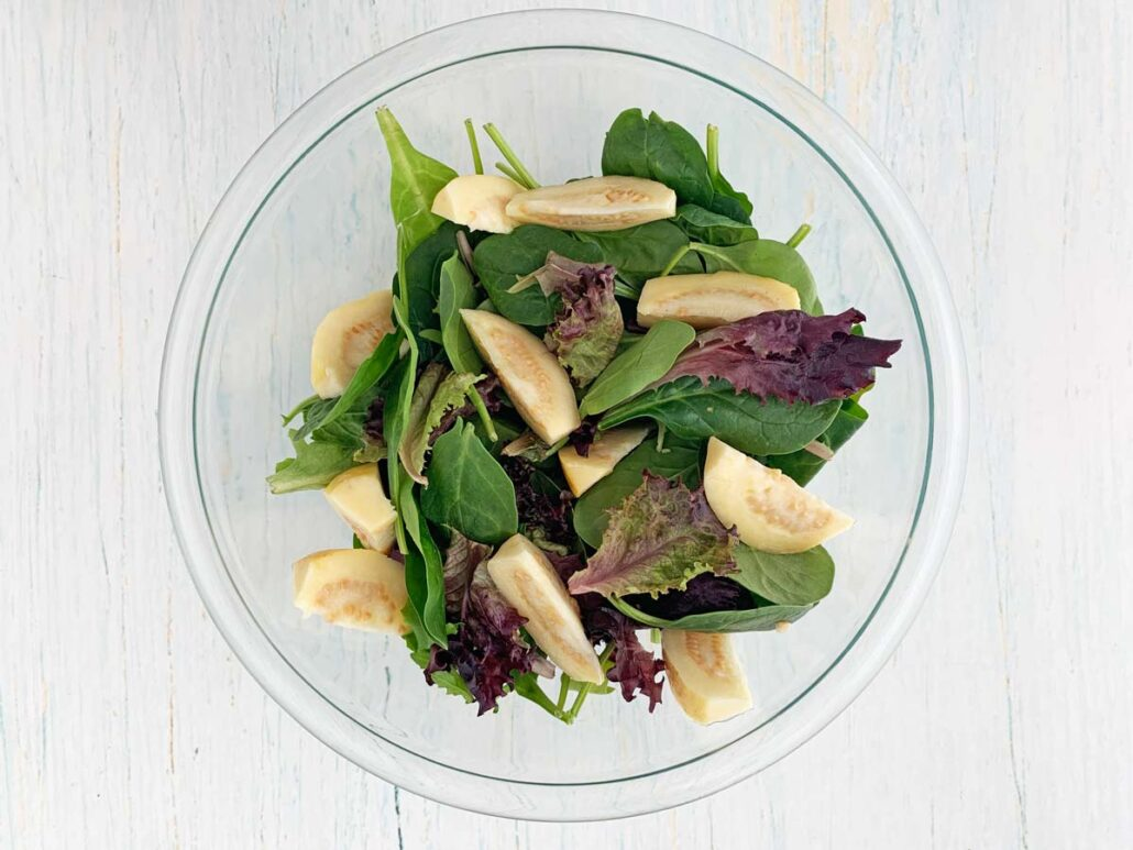 glass bowl with mixed greens and guava