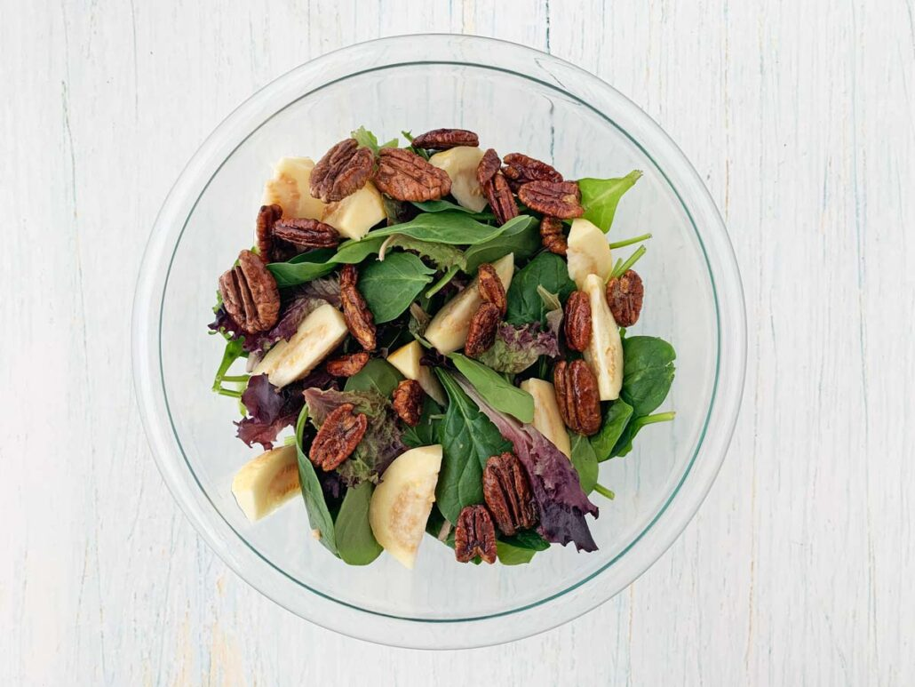 glass bowl with mixed greens, guava, and candied pecans