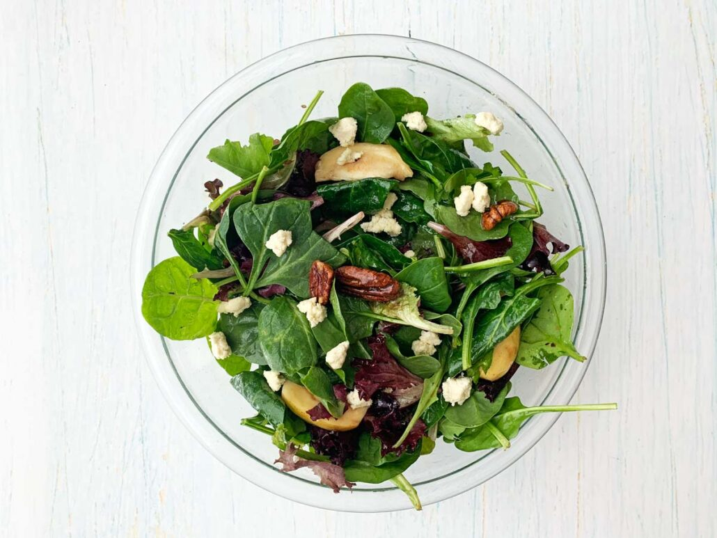 glass bowl with salad, queso fresco and candied pecans