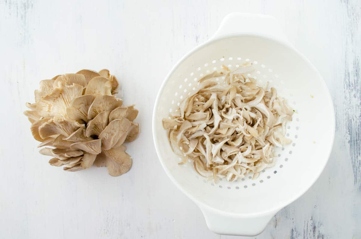 oyster mushrooms in a colander on a white surface