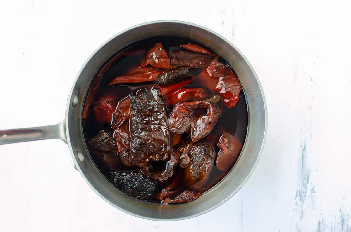 dried chiles soaking in a pot with water