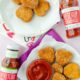 two plates of vegan chicken nuggets and two bottles of ketchup