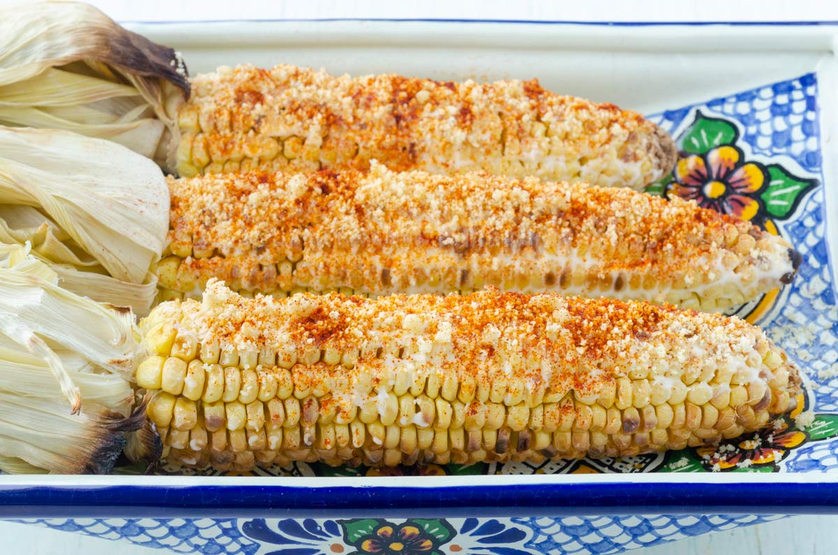 3 cobs of corn covered in mayo, chile powder, and cheese