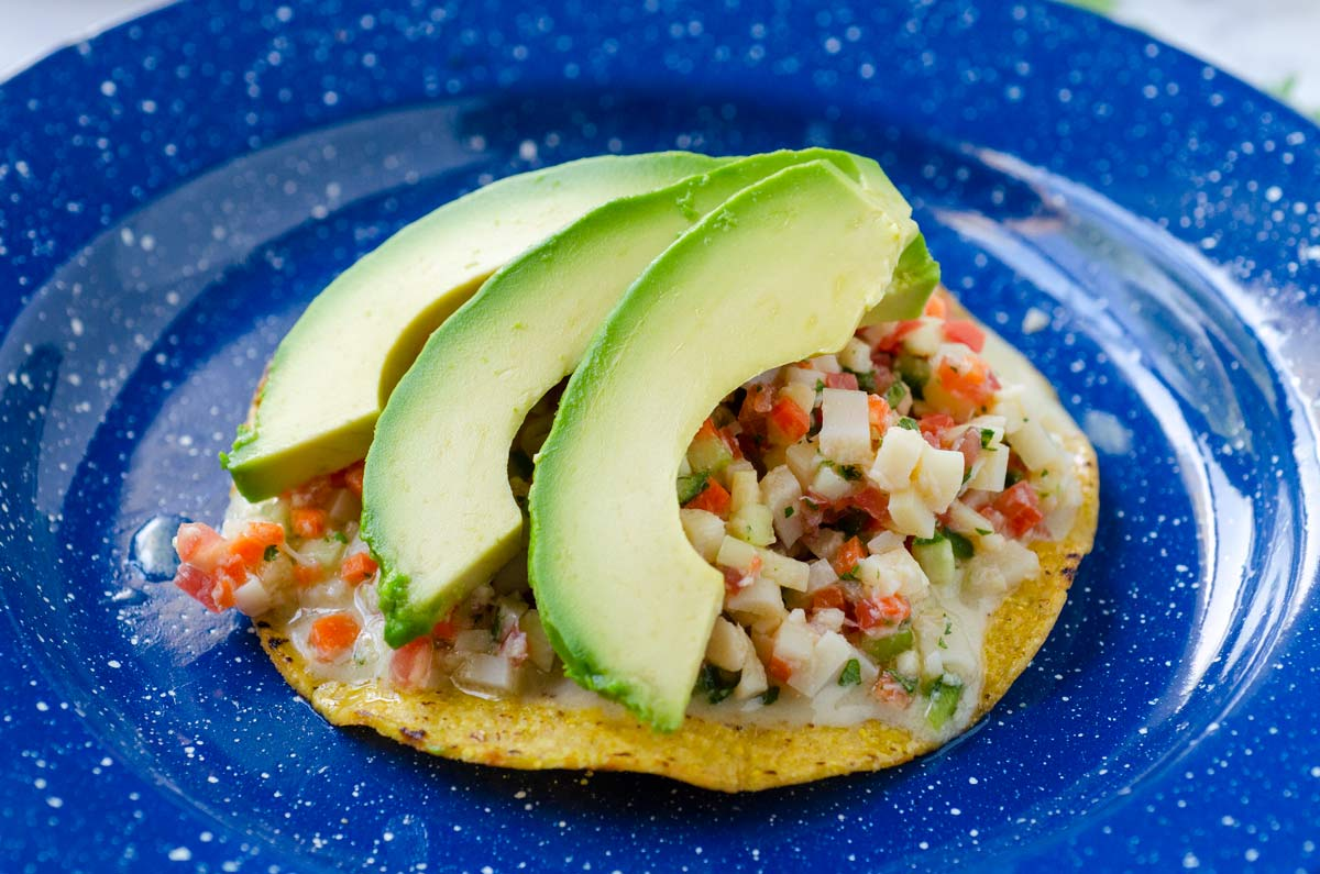 a close up of a baja ceviche tostada topped with avocado on a blue plate