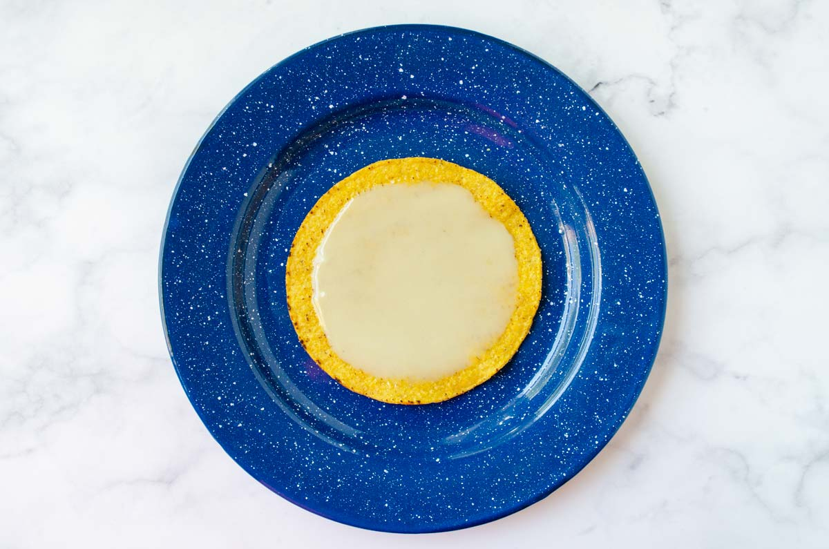 a blue plate with a tostada slathered in mayo