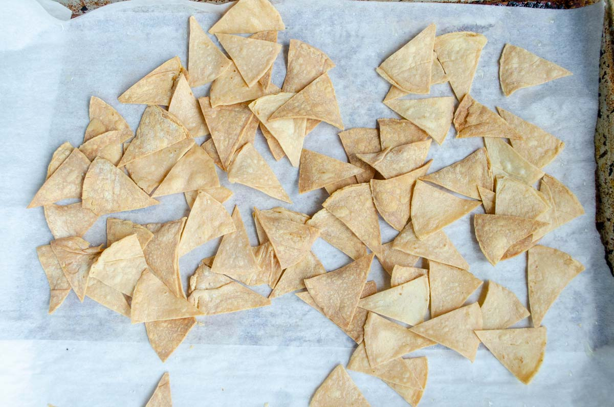 baked tortilla chips on a sheet tray lined with parchment