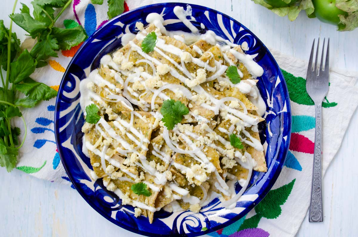 a bright blue plate with chilaquiles verdes topped with crema and cheese
