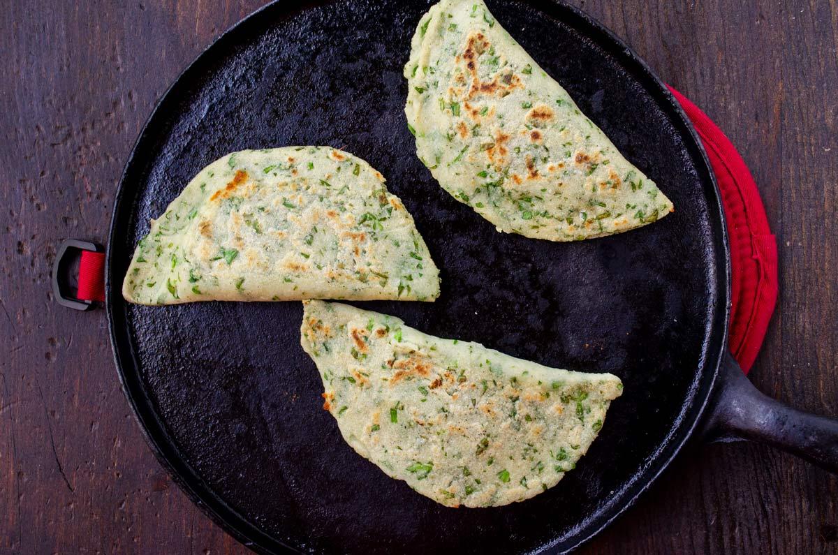 three empanadas on a comal