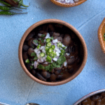 heirloom beans in red mole sauce in a clay bowl on a blue background