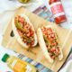 two Mexican hot dogs on a striped napkin with a marble background surrounded by ingredients