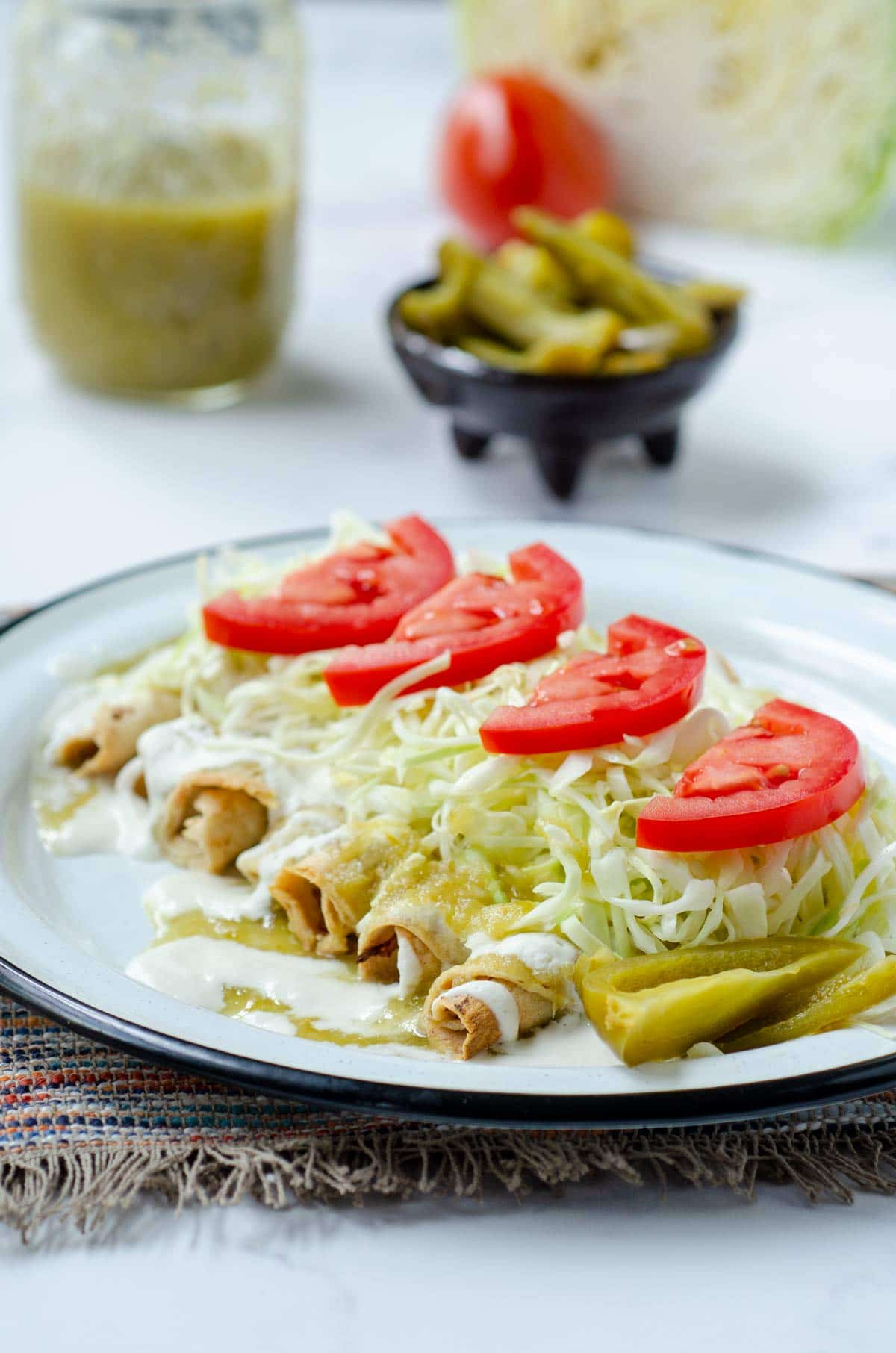 crispy rolled tacos topped with cabbage and tomatoes on a white plate