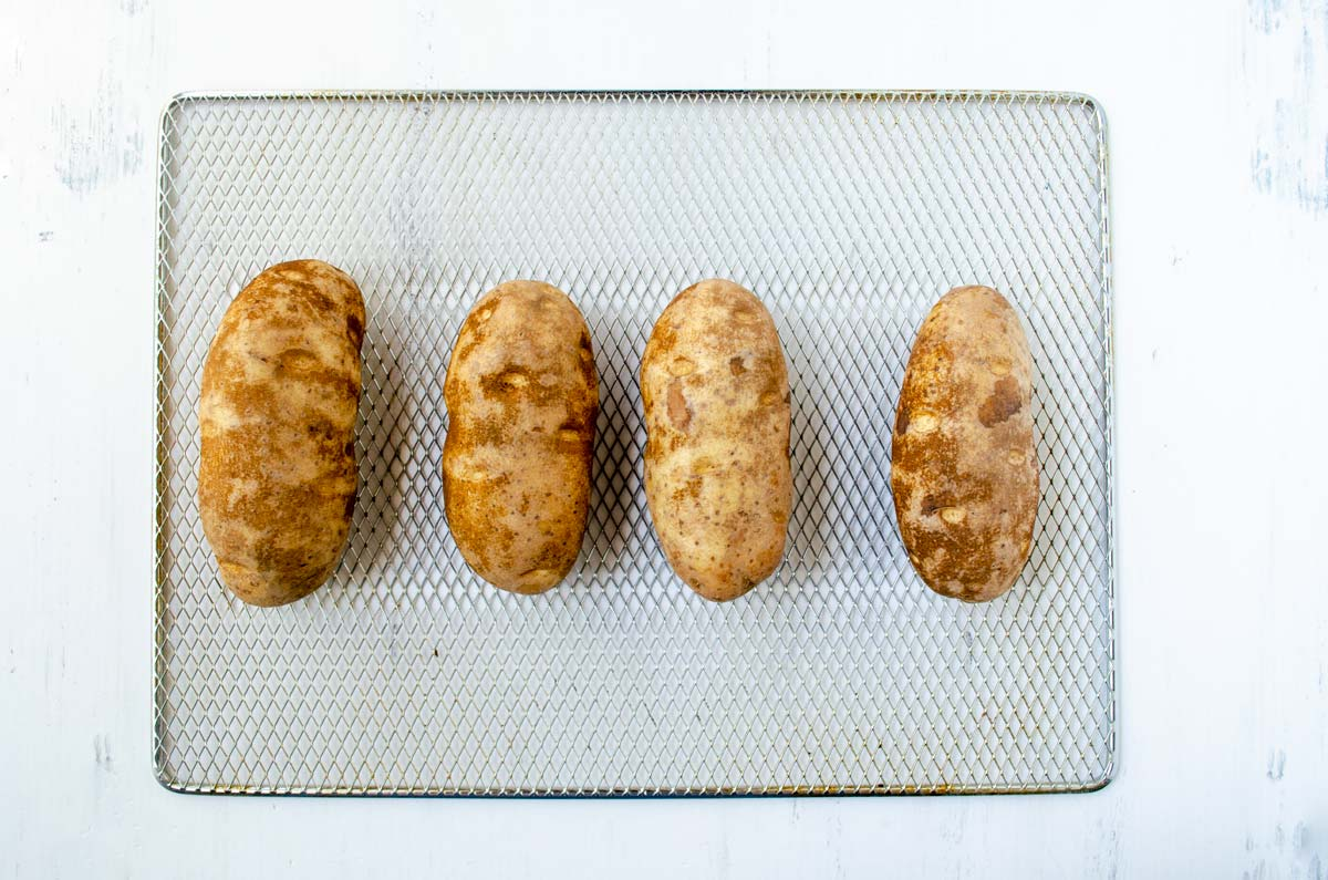 four russet potatoes on a rack