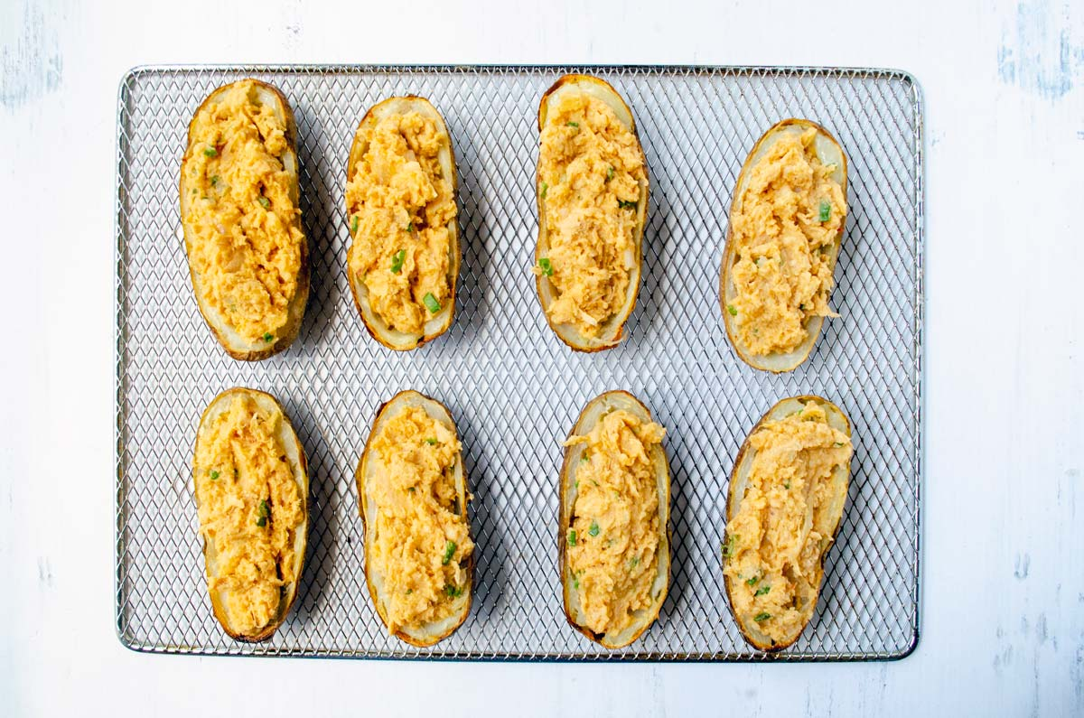 eight potatoes on a rack cut in half and filled with buffalo chicken