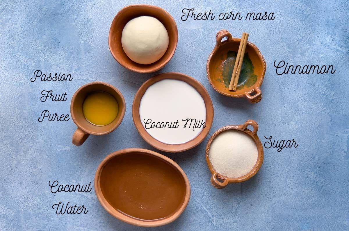 ingredients for nicuatole in small clay pots, coconut milk, cinnamon, masa, coconut water, passion fruit puree,