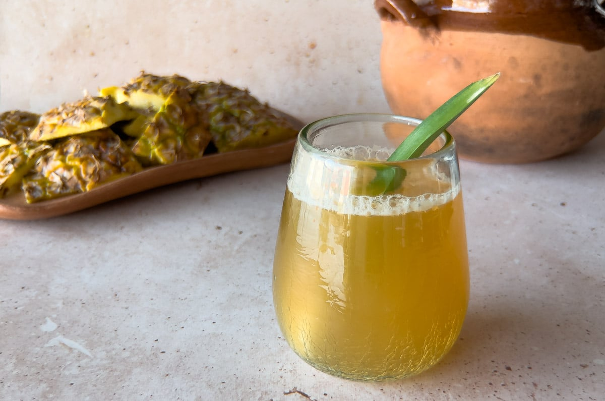 glass of pineapple fermented drink with a pineapple leaf as a garnish