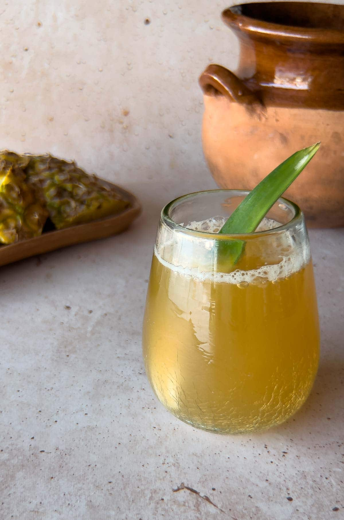 glass of pineapple probiotic drink on a beige background