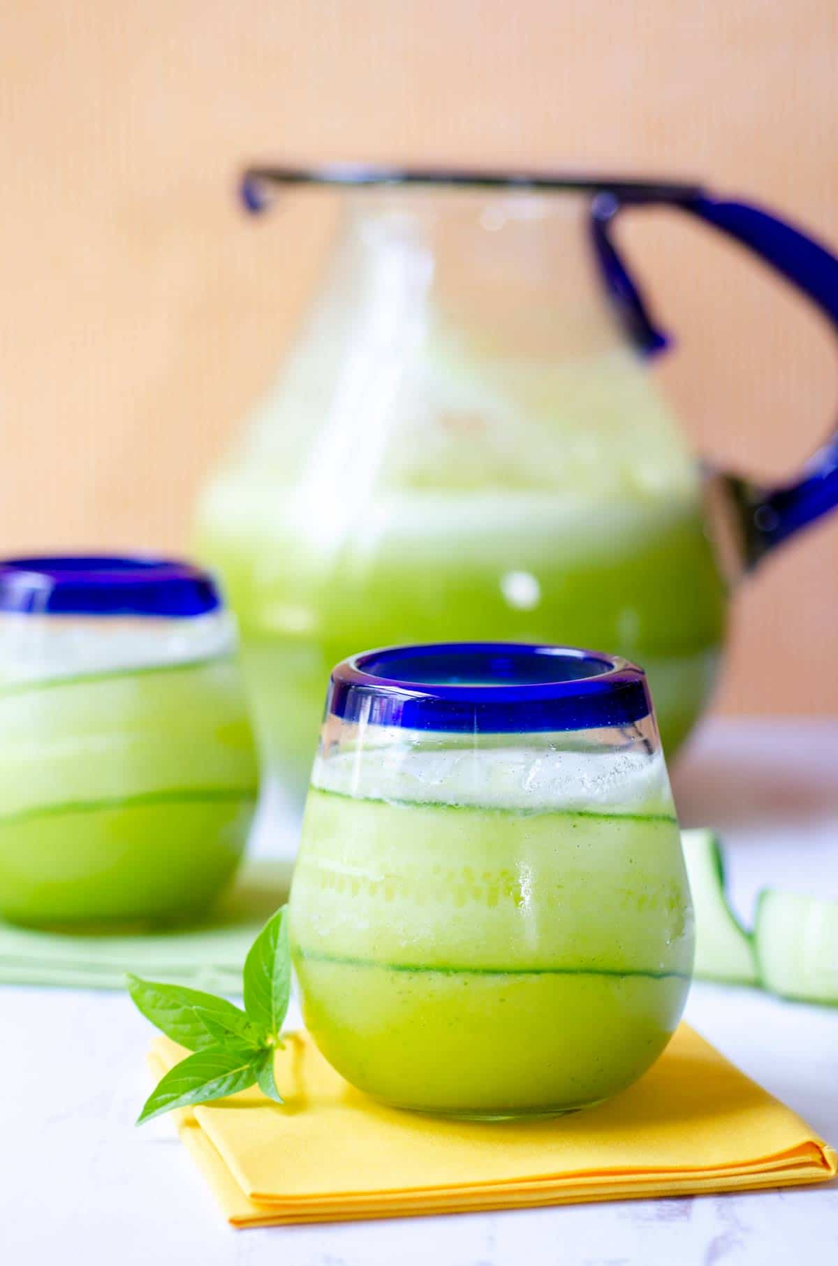two glasses filled with pinaepple cucumber agua fresca with a pitcher behind