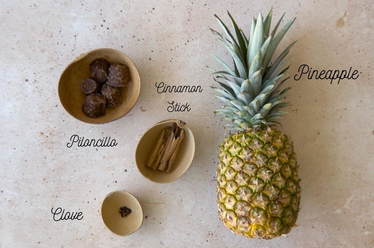 pineapple, cinnamon stick, clove, and piloncillo on a beige background