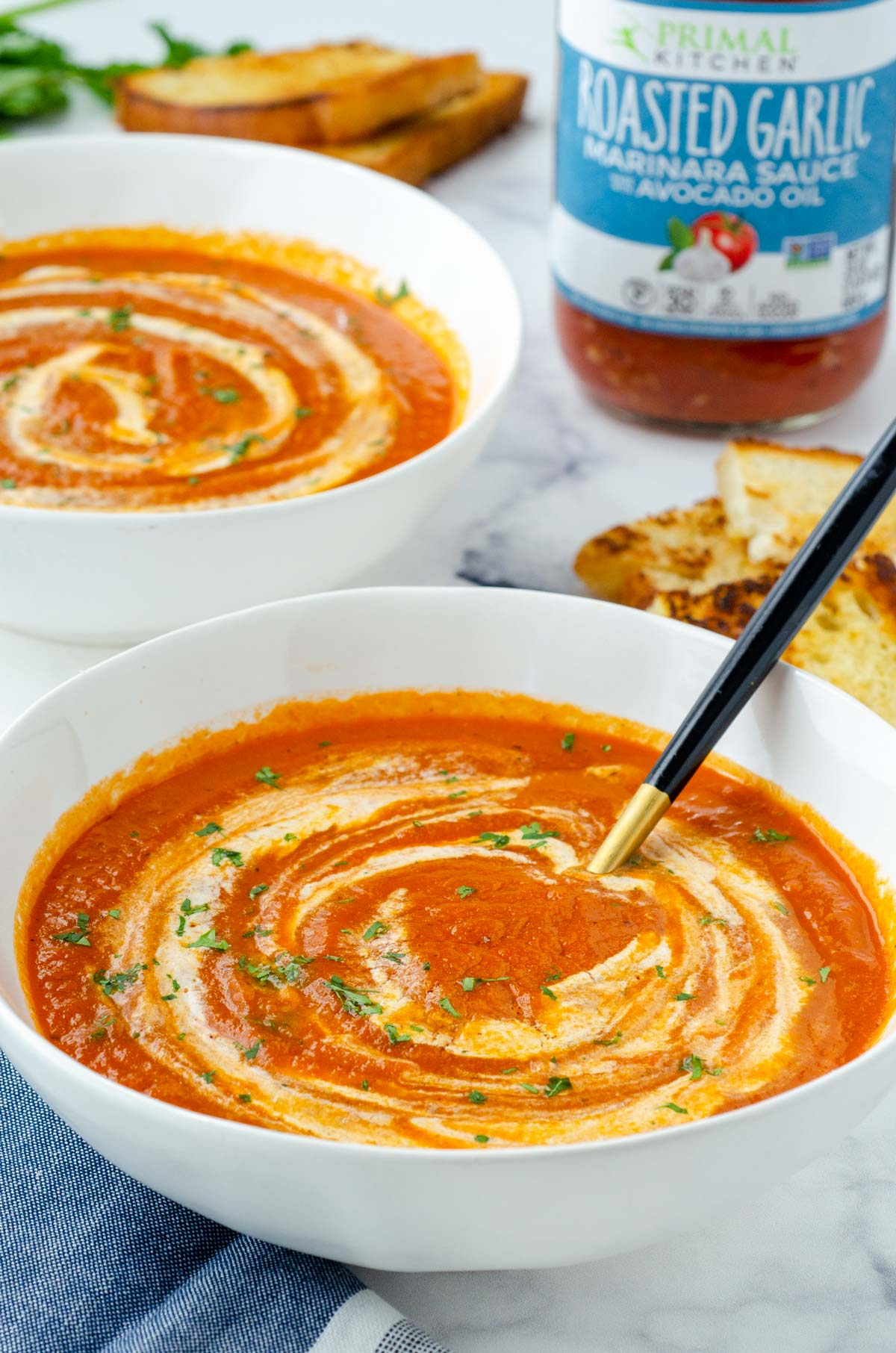 two bowls of tomato soup with a jar of marinara sauce behind them