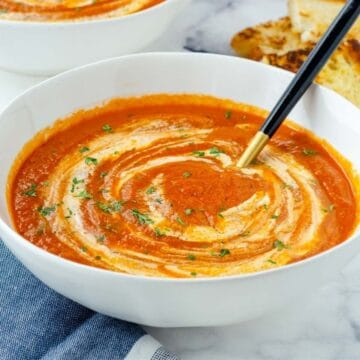bowl of chipotle tomato soup with a gold and black spoon