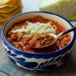 vegan pozole in a white and blue talavera bowl on top of a linen napkin with a spoon digging in
